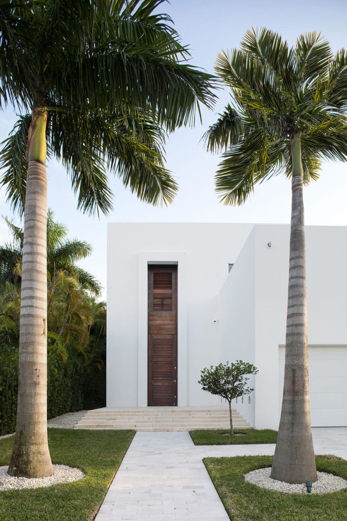 A lovely, if a bit simple row of landscaping leading up to the two-story wooden front door sans mirrors. Enormous palms line the walkway, with a single small fruit tree near the steps leading up to the front door.