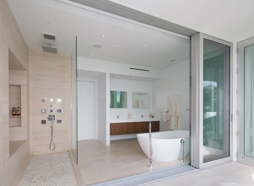 Moving upstairs to the primary bathroom, we see the way glass panels are used to visually separate the shower area from the rest of the bathroom, and accordion sliding panels can be retracted to expose the bathroom to an outdoor terrace overlooking the pool and the bay.