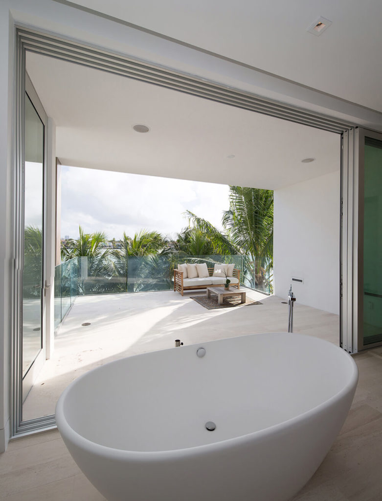 From inside the primary bathroom we can see the outdoor terrace, which is surrounded by glass balustrades and shaded from view by a series of tall palms that surround the back of the propert