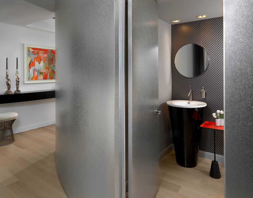 As we round the corner, we are presented with a long hallway stretching to either side of the condominium. A curved silver-leaf wall opens up into the small powder room, which features a cone-shaped pedestal sink and matching end table. The geometric wallpaper on one wall really pulls the eye into the room.