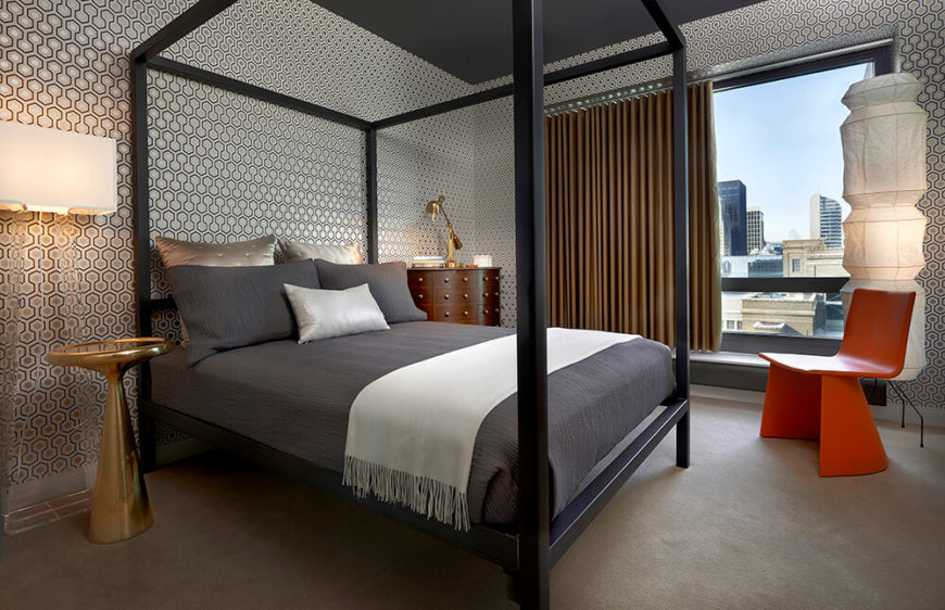 The geometric guest bedroom features a four-post bed, a charcoal ceiling, a bold accent chair in orange, golden accents, and a fantastic view of the Chicago skyline. The room is wallpapered in a geometric pattern, which is incredible.