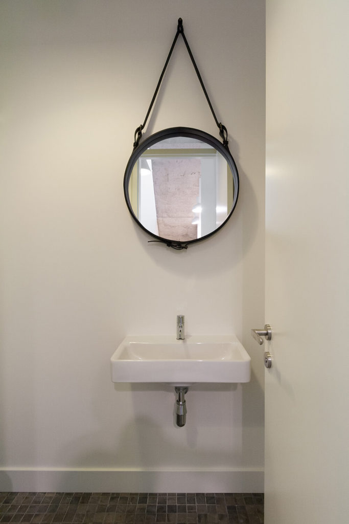 This small half bath features a floating sink and a unique hanging mirror suspended by belt straps. This appears to be the only source of color and decor in the small room.