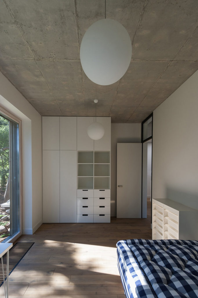 One of the two guest bedrooms, this one looks out into the yard and offers up plenty of built-in storage. The pale wood floors balance the white walls and storage. Large sphere pendant lights are suspended from the cement ceiling.