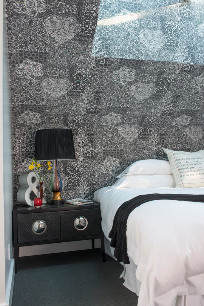 The bedside table features unique chrome hardware and inner storage, supporting artful pieces like the colored glass lamp. The detailed wall textures provide high contrast with the plain white bedding and grey carpet.