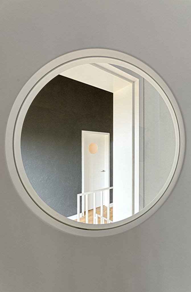 An interesting aspect of the house, the doors each feature a small circular wind0w to peek out of, revealing an artistic view of the home and a unique perspective on the different spaces.