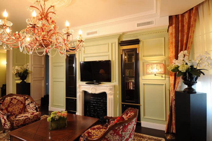 The living room centers on a white marble fireplace, flanked by a pair of black painted bookshelves with glass cabinetry. Rich wainscoting makes for detailed surroundings, while the ornate armchairs sit below an opulent chandelier.