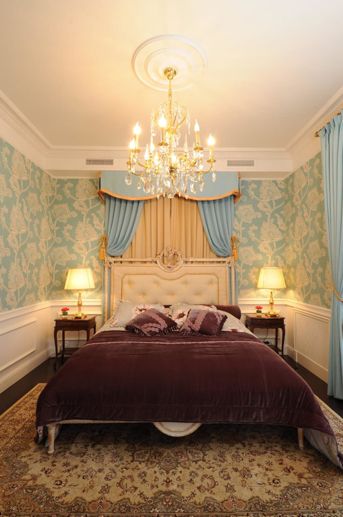 The primary bedroom is highlighted by the presence of sky blue on the wallpaper, drapes, and headboard framing. The lower wall is decked in white wainscoting, adding a bold contrast to the rich, dark hardwood flooring.