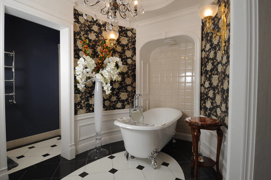 The primary bathroom centers on a circular space with a classic claw foot tub over black and white tile flooring. Floral wallpaper in a different shade helps define this distinctive area of the home.