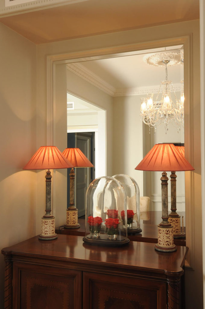 A rich carved wood display cabinet holds a pair of traditional lamps and a glass dome display for flowers, in front of a large mirror designed to expand the visual space of the room.