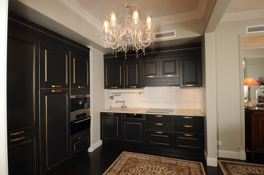 The kitchen is defined by dark wood cabinetry with gold accents, a bold twist that contrasts deeply with the white tile backsplash.