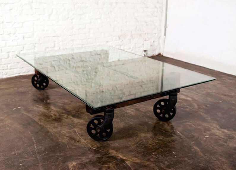 In an inspired twist on the industrial cart design, we see the classic underpinning of this table supporting a sleek glass panel in lieu of the original wood construction. This creates an interesting hybrid of modern and industrial styles and a completely unique coffee table.