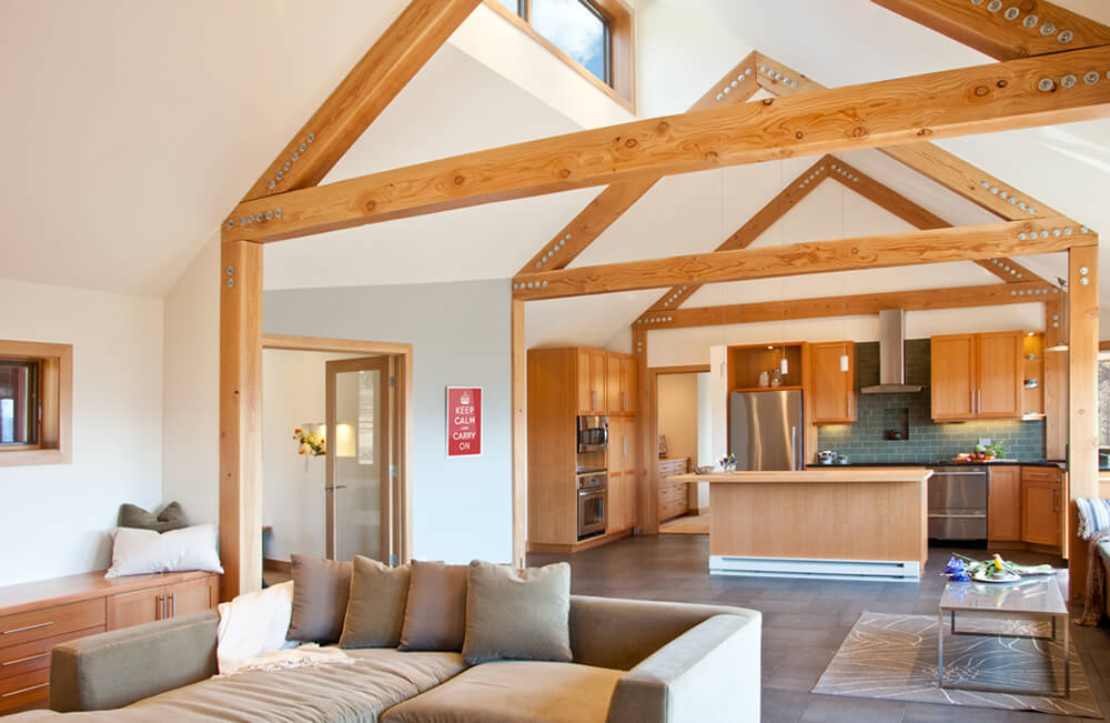 A great room under the vaulted ceiling with exposed beams and is surrounded by white walls.