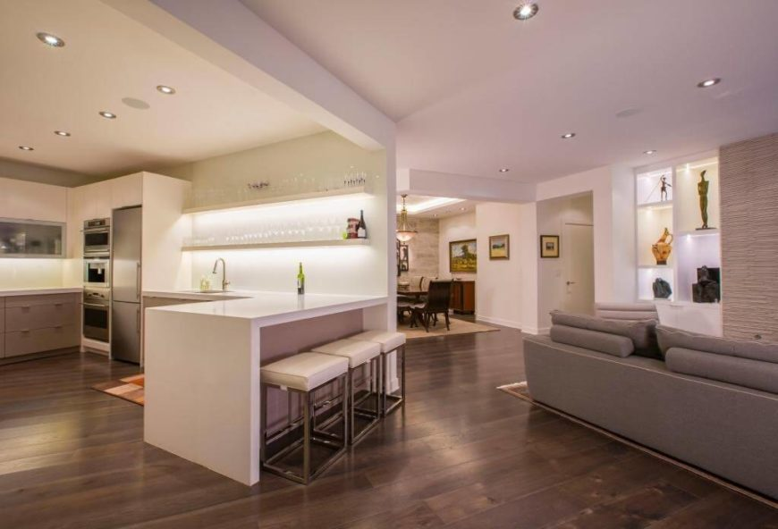 White kitchen with stainless steel appliances and smooth counters with hardwood floors and recessed lights.