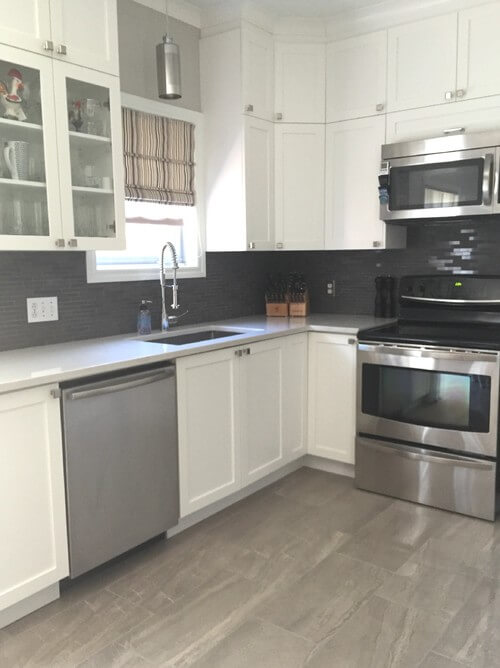 Kitchen with white cabinetry and stainless steel appliances along with tiles flooring and backsplash.