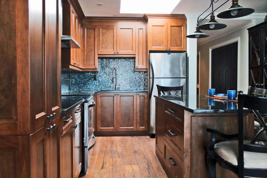 Kitchen with walnut cabinetry and hardwood flooring along with unique backsplash and breakfast bar.