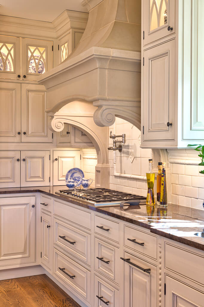 Kitchen covered by white walls and white cabinetry featuring white brick backsplash and solid countertops.