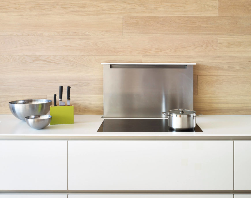 Kitchen showcasing snooth white countertop and a wooden backsplash along with smart appliances.