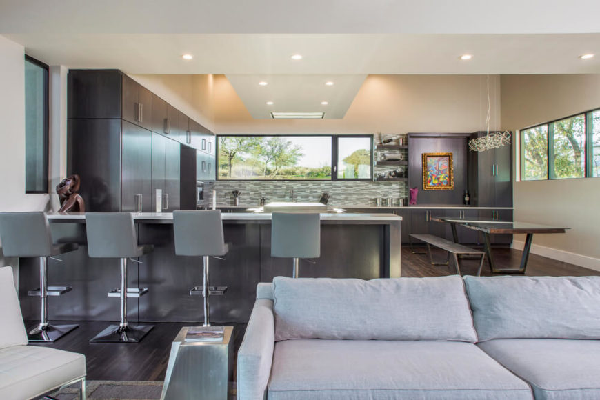 Modern large kitchen with stylish cabinetry and hardwood flooring along with a breakfast bar and a dine-in table set.
