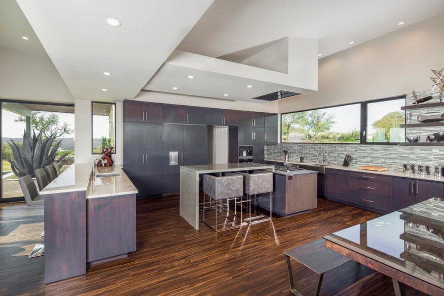 Large kitchen with stylish wooden cabinetry and marble countertops along with a breakfast bar and dine-in table set.
