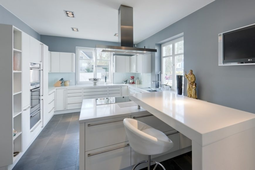 Modern kitchen with gray walls and white cabinetry along with smooth white countertops and center island with a built-in desk.