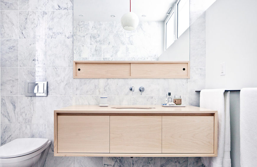 The bathroom is awash in rich marble, contrasting deeply with the light wood tones of the vanity and mirror shelving. This helps stylistically define the bathrooms from the rest of the home.