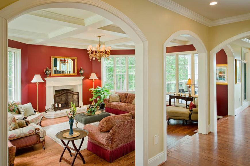 Voici le salon après!  Les plafonds à caissons et les garnitures blanches égayent l'espace, tout comme l'ajout de fenêtres supplémentaires.  Les murs rouges audacieux apportent de la couleur et de la vie à la pièce tandis que les larges arches définissent la pièce comme un espace séparé tout en la laissant ouverte sur le reste de la maison.  La cheminée a été agrandie et dotée d'un manteau approprié.