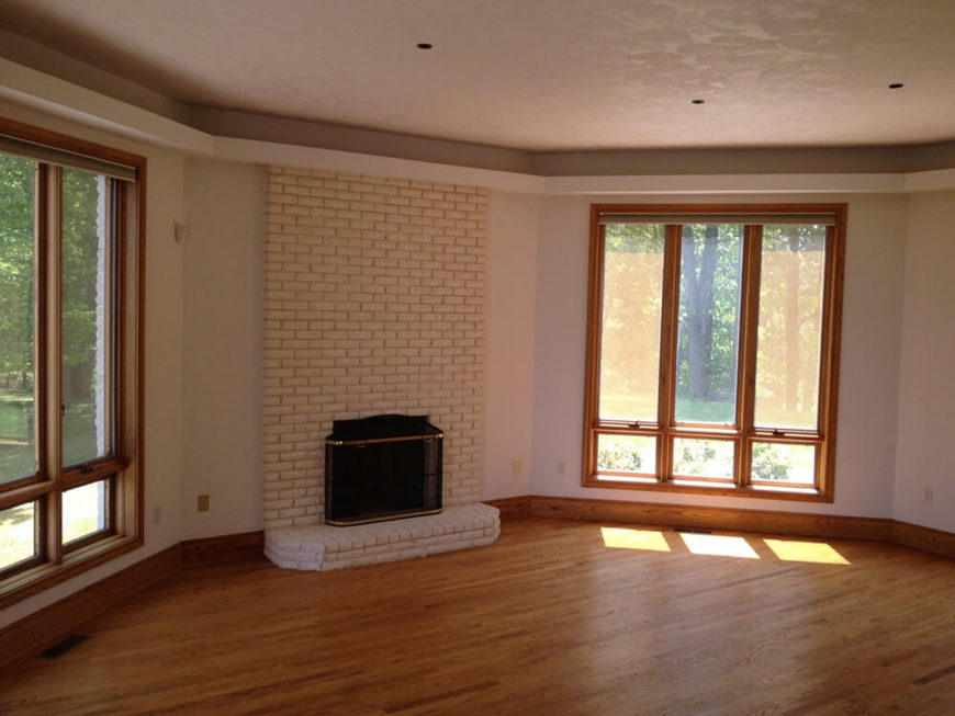 Here is the before living room complete with small windows, small fireplace, and brick mantle. The wood floor is nice in this room but could use a bit of brightening up. A recessed ceiling casts a shadow on the ceiling of the room, making it appear darker than it actually is and giving the room a more enclosed feeling.