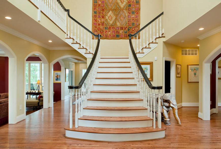 Bien mieux!  Ils ont conservé le bois naturel des escaliers pour le haut de chaque marche et ont rafraîchi l'escalier avec une couche de peinture blanc crème, permettant à la couleur du bois de ressortir contre le blanc.  La coloration foncée des rampes compense les couleurs vives de la pièce mais agit également comme une focalisation visuelle pour amener les yeux au deuxième étage.