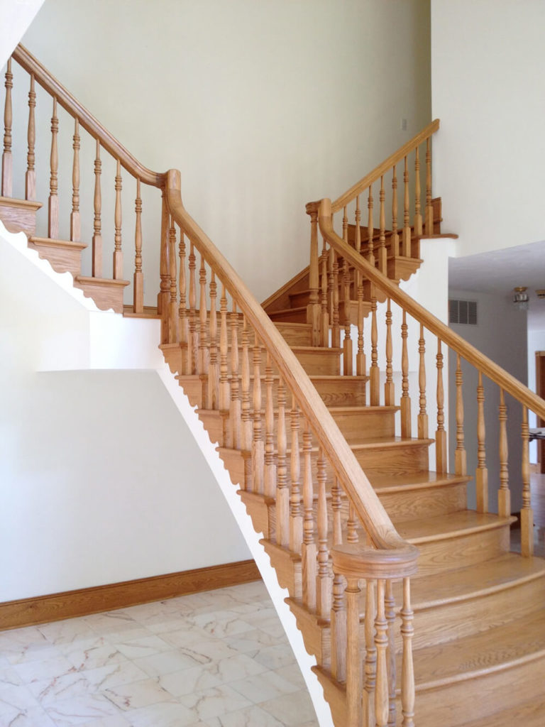 When compared to the white walls, these stairs seem dark and heavy, cutting into the bare walls without any preamble. The wood of the stairs is gorgeous so maintaining it was a goal of the designers. That, of course, did not mean that they couldn't give these lovely stairs a facelift.