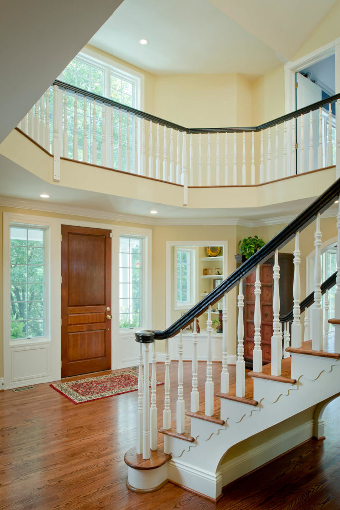 Open and airy, the addition of more windows and the removal of the steeply arched ceiling helps make the space feel larger, even though the balcony was added above the door. Wood floors make the home feel warmer and more welcoming. Little details - like the woodwork under and along the sides of the stairs - add to the overall design.