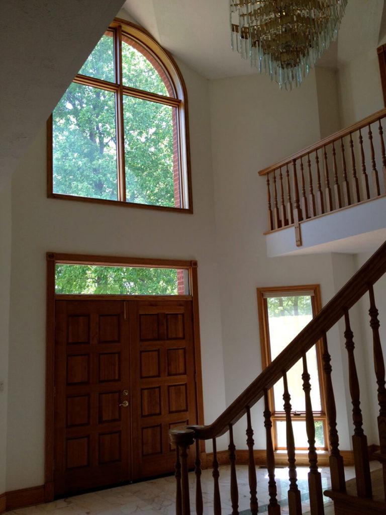 Le hall de la conception originale semble ouvert bien que très sombre malgré la grande fenêtre cintrée au-dessus de la porte.  Des accents de bois naturel et des murs blancs complètent les sols en marbre.  Il y a une sensation datée dans la conception de l'entrée qui pourrait certainement utiliser un nouveau look.