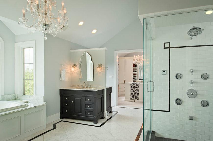 Les vanités doubles, une de chaque côté du mur partiel, utilisent bien l'espace de la salle de bain.  Ici, vous pouvez également voir la douche à l'italienne aux parois de verre qui suit le design simple en noir et blanc de la pièce avec un carrelage de métro de merde et un sol en carrelage noir.  En arrière-plan, vous pouvez voir le dressing attaché à la salle de bain.