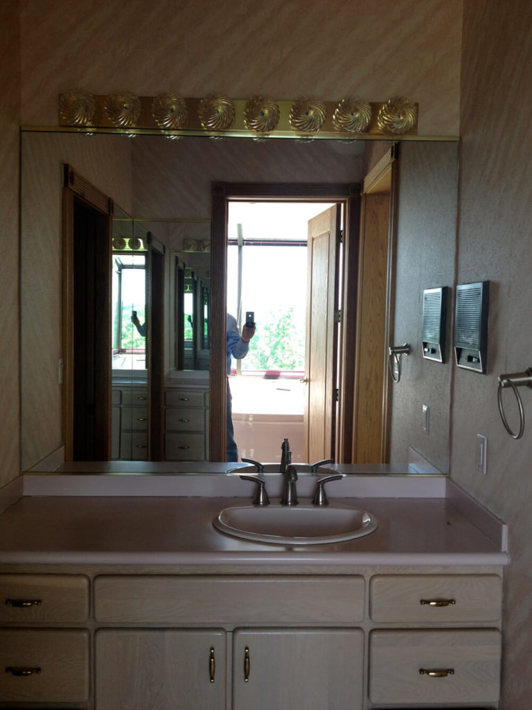 The old vanity area was stuck in its own little room, making the space dark and cramped if more that one person wanted to use it. The pink counter tops, wallpaper, and light fixture really dates this space.