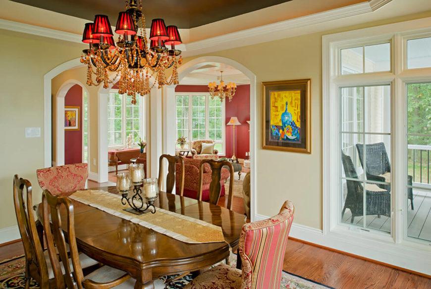 La salle à manger s'ouvre sur le salon et le couloir.  Il porte la couleur rouge et or  schéma de la maison bien tout en intégrant des antiquités et des tissus vus dans les autres pièces.  Ce lustre est assez étonnant avec ses perles ambrées, ses cristaux et ses petites nuances rouges.