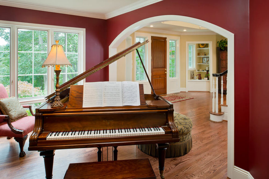 The front parlor with grand piano and a view of the foyer in the back ground. They matched the newly installed wood floor to the already present ones to allow that whole house to flow.