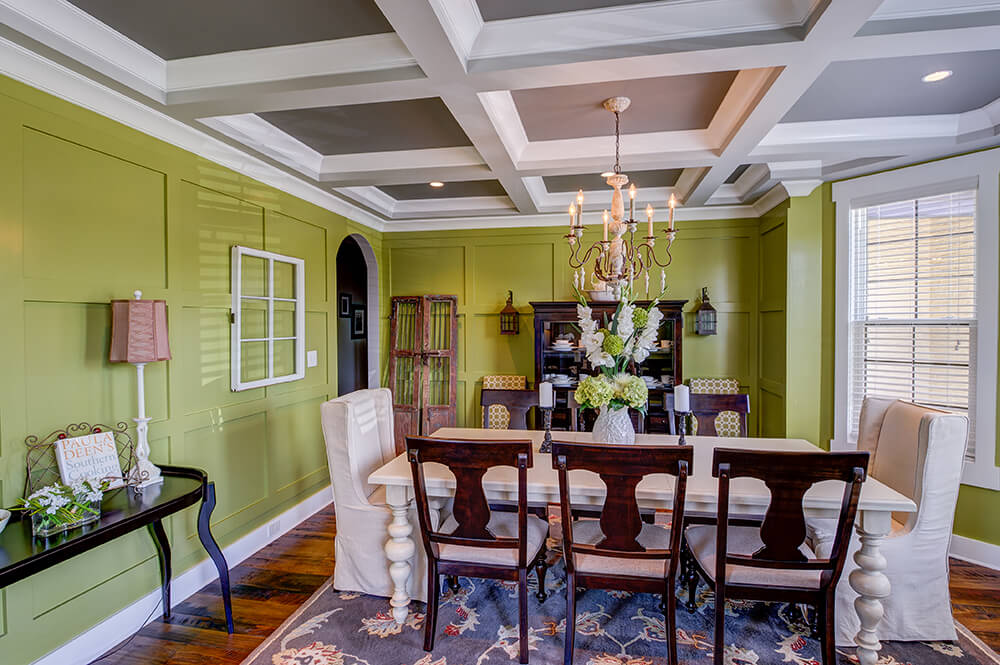 An olive green dining room showcases recessed wainscoting walls and coffered ceiling. It has a white dining table surrounded by cushioned wooden and skirted wingback chairs.