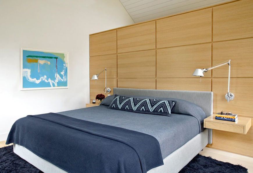 This angle of the bedroom reveals the full bed, and we will see that the other side of the bed has a matching bedside shelf and mounted adjustable lamp, once again an example of the designer appreciating the aesthetic appeal of symmetry. The vibrant blue artwork on the wall contrasts the subtle tones in the rest of the room well.