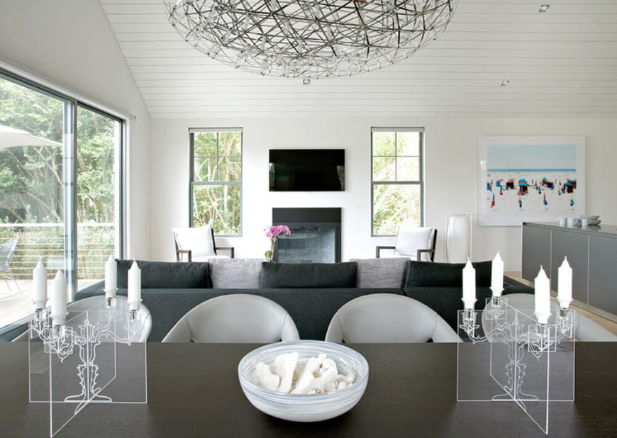 This angle from behind the dining table shows how symmetrical this house really is. From the placement of each chair to the location of each window, this house has been designed to keep every space connected, while maintaining a constant symmetrical appeal. The white and black theme is prevalent in this home, only a few decorations and paintings hanging on the wall stray from this color scheme.