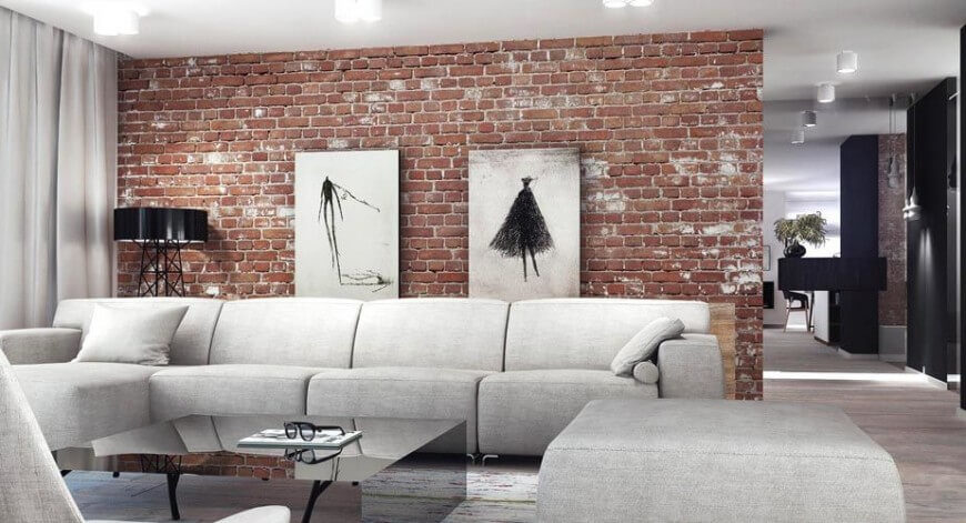 The weathered look of this read brick is balanced by the color tone of the rest of the room. Art may look particularly striking against a red brick wall.