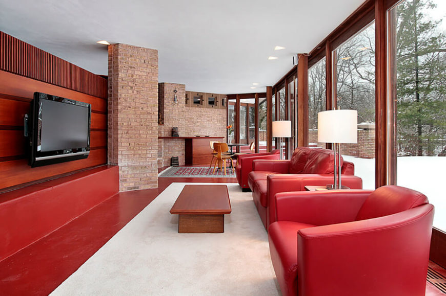 Brick certainly plays well with others. In this room, the red theme works well against the white lampshades and carpet. The red brick helps reinforce the red color scheme.