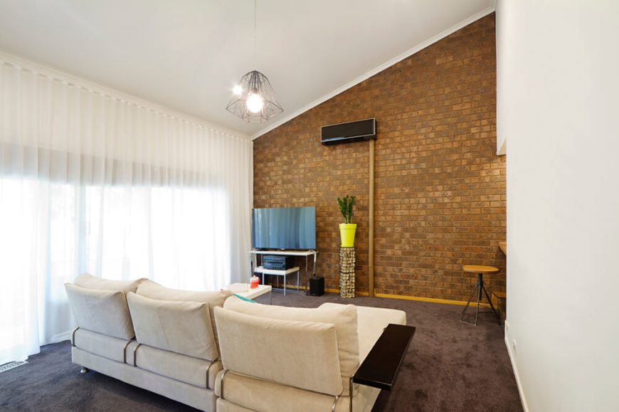 Many times, just one wall (typically an outer wall) of a room will have brick. Set against the white curtains and sofa, this small brick wall prevents the room from becoming too stuffy.