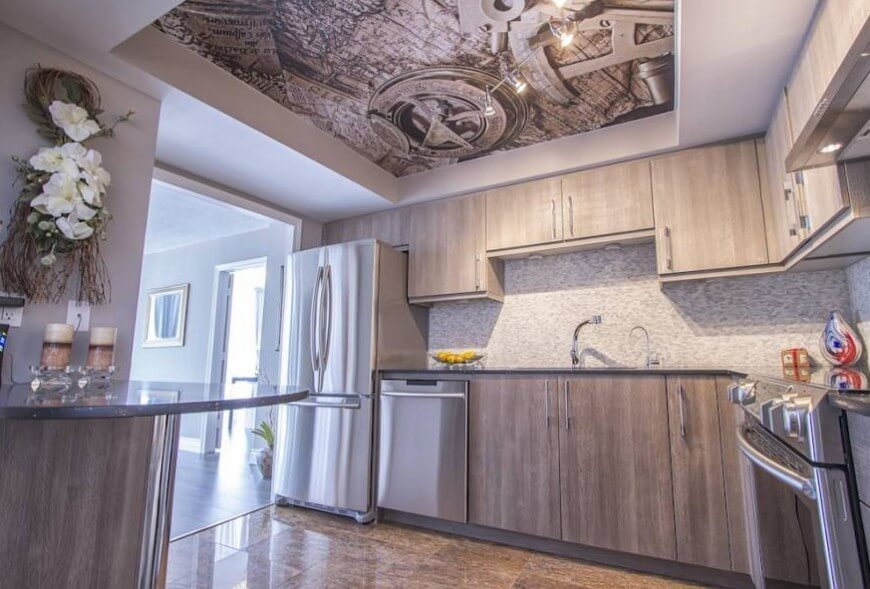 Beneath a bold art print on the ceiling of this kitchen, we see light grey stained wood cabinetry, a micro tile backsplash, and rich marble flooring. The sheen of stainless steel accents the space well.