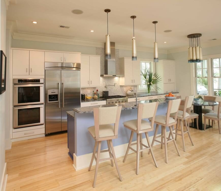 A series of pendant lights hang above the rich natural wood flooring of this kitchen, spiked with sleek white cabinetry and a two-tier island that provides plenty of dining space for a quartet of bar stools. The stainless steel appliances make for a delicate contrast in this example.