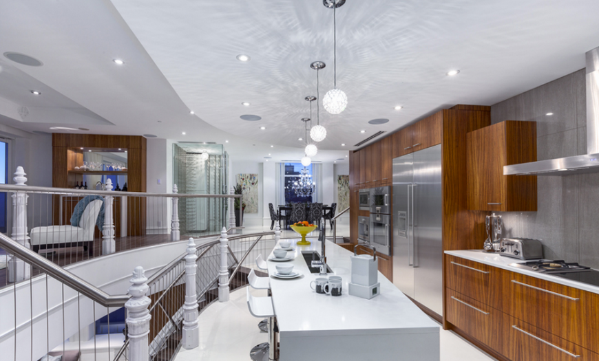This kitchen is an absolute riot of color and texture, with bright natural wood cabinetry holding stainless steel appliances at right, and a pristine white island at center. Within a larger open design area, the kitchen is defined by this high contrast look.