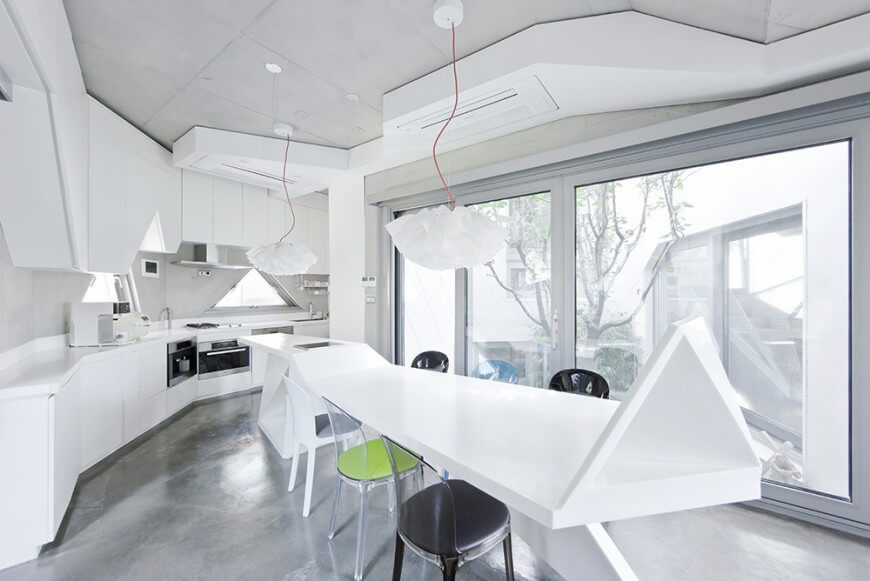 Our final kitchen is an astonishing modern creation focused on irregular geometric shapes. Bold white colors the island, countertops, and cabinetry while soft grey informs the flooring. Bright natural light pours in through massive full height windows, reflecting off the subtly powerful stainless steel appliances.