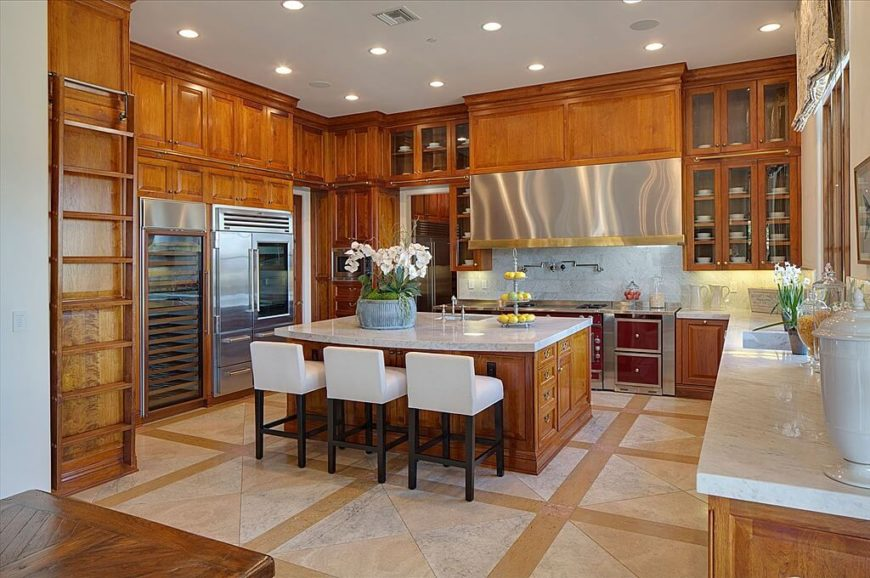 With a very tall ceiling, there's plenty of room for an abundance of warm wood cabinetry. The kitchen even features a ladder and rail system, much like a library, for reaching the upper cabinets. In addition to white marble, the space is spiked by the appearance of stainless steel appliances.