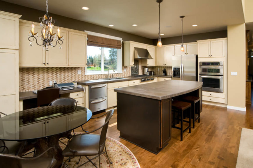 The highly textural tile backsplash of this kitchen adds an attention grabbing layer to this contemporary kitchen, sandwiched between layers of light hued cabinetry over a hardwood floor. The massive island features a light brown countertop and dark stained wood body, in sharp contrast to the bright stainless steel appliances.