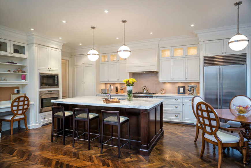 Rich, dark stained hardwood flooring contrasts with pristine white cabinetry in this large, open design kitchen. Stainless steel appliances add a flash of sleek modernism, but the whole room is anchored by the dark wood island with marble countertop.