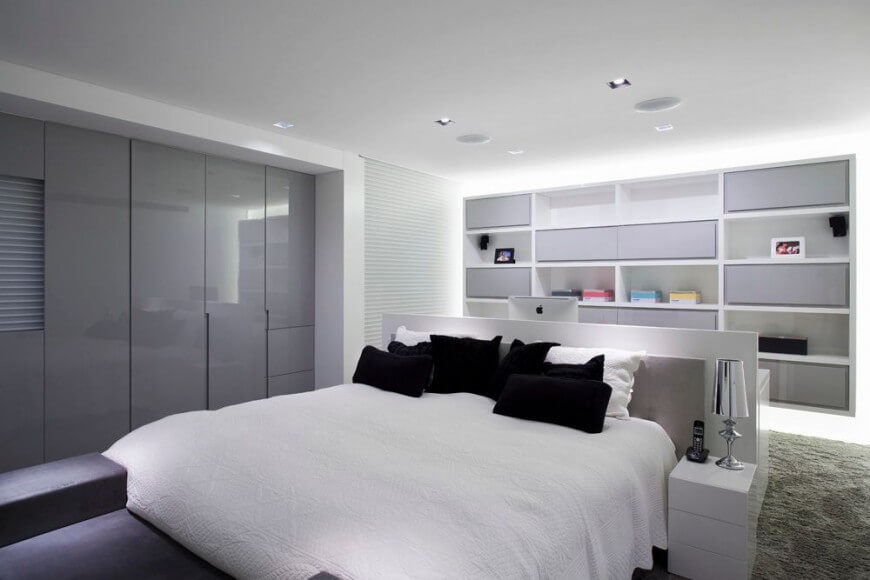 White and grey tones fill this bedroom, contrasted only by the black accent pillows and colorful boxes on the shelves. The sleek wall panels help to reflect light back into the room. While it is almost unnoticeable, you can see that there is a computer right behind the bed, suggesting that there is a desk space doubling as a head board.