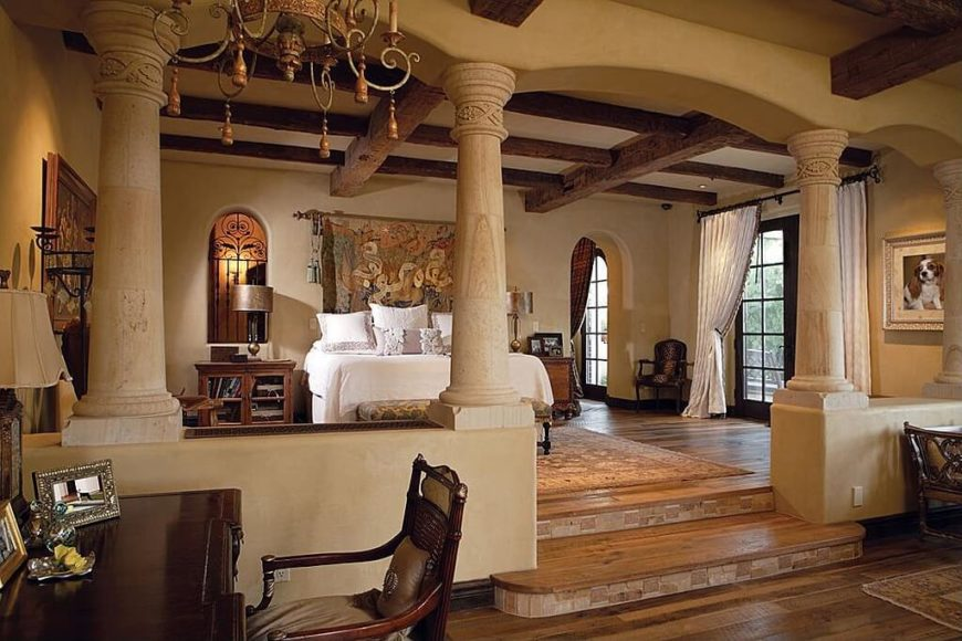 This massive bedroom actually has two levels, separated by a set of large textured columns. The floors are a rich stained hardwood. The walls are a light creme color, which matches the ceiling. There are large rafters crossing each other on the ceiling, which help to give the room some depth. The upper level features the bed and side tables, while the lower contains the working desk.